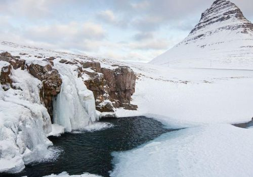 Kirkjufell mountain and the frozen waterfall Kirkjufellsfoss on the Snaefellsnes peninsula in the snow in winter, Iceland.