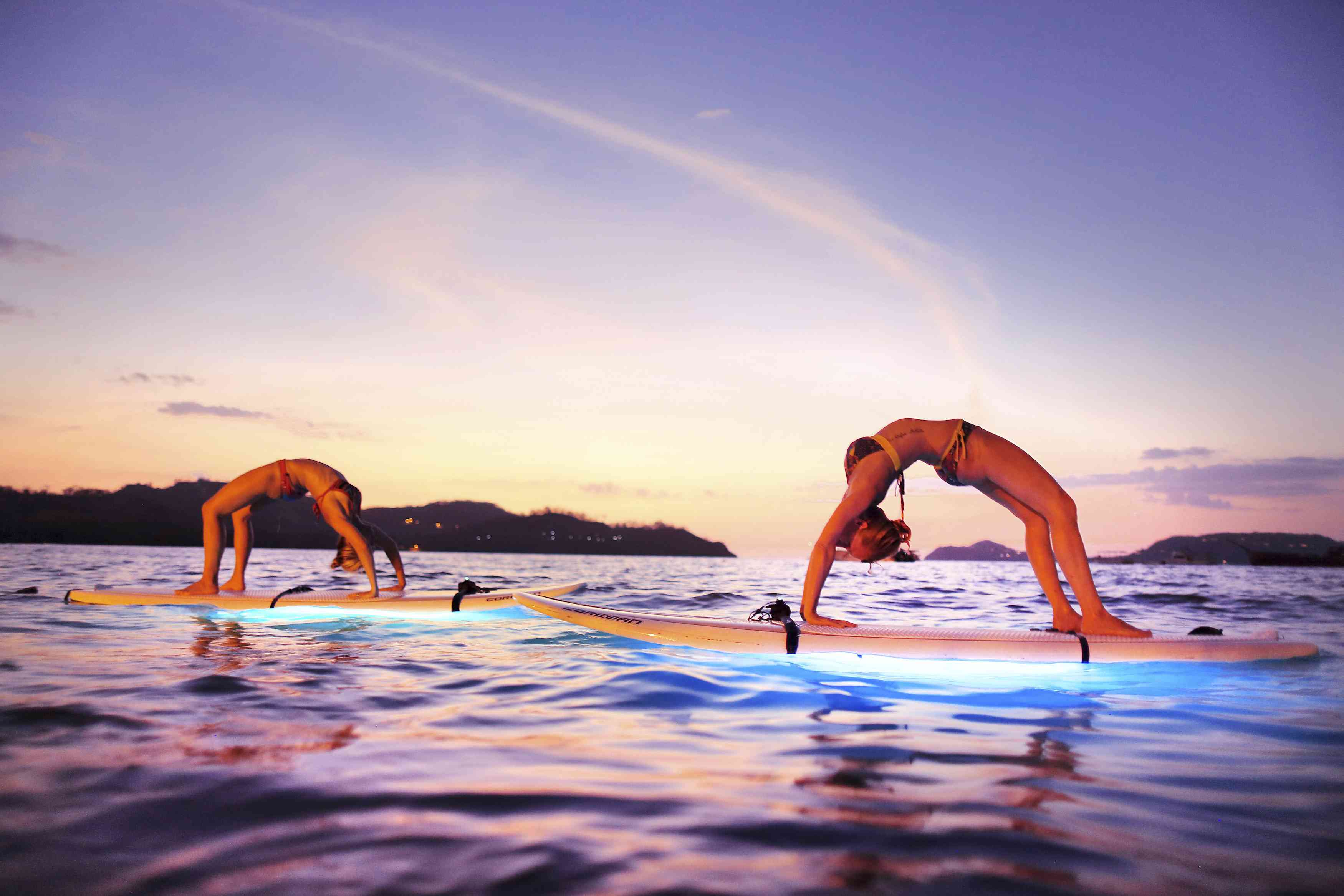 Couple doing paddle board yoga in Costa Rica