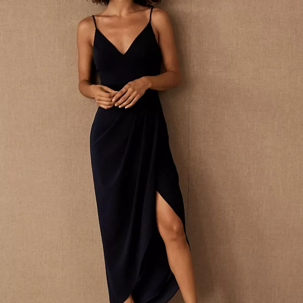 Model in a dark blue V-neck dress with a tulip skirt with a gathered waist