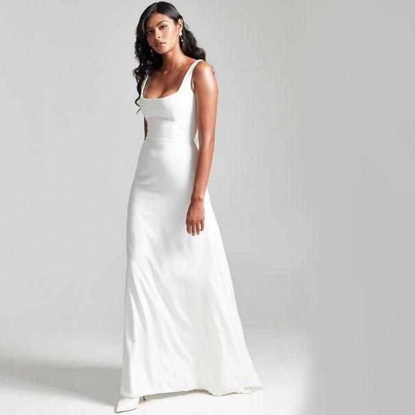 Model in simple white wedding dress.