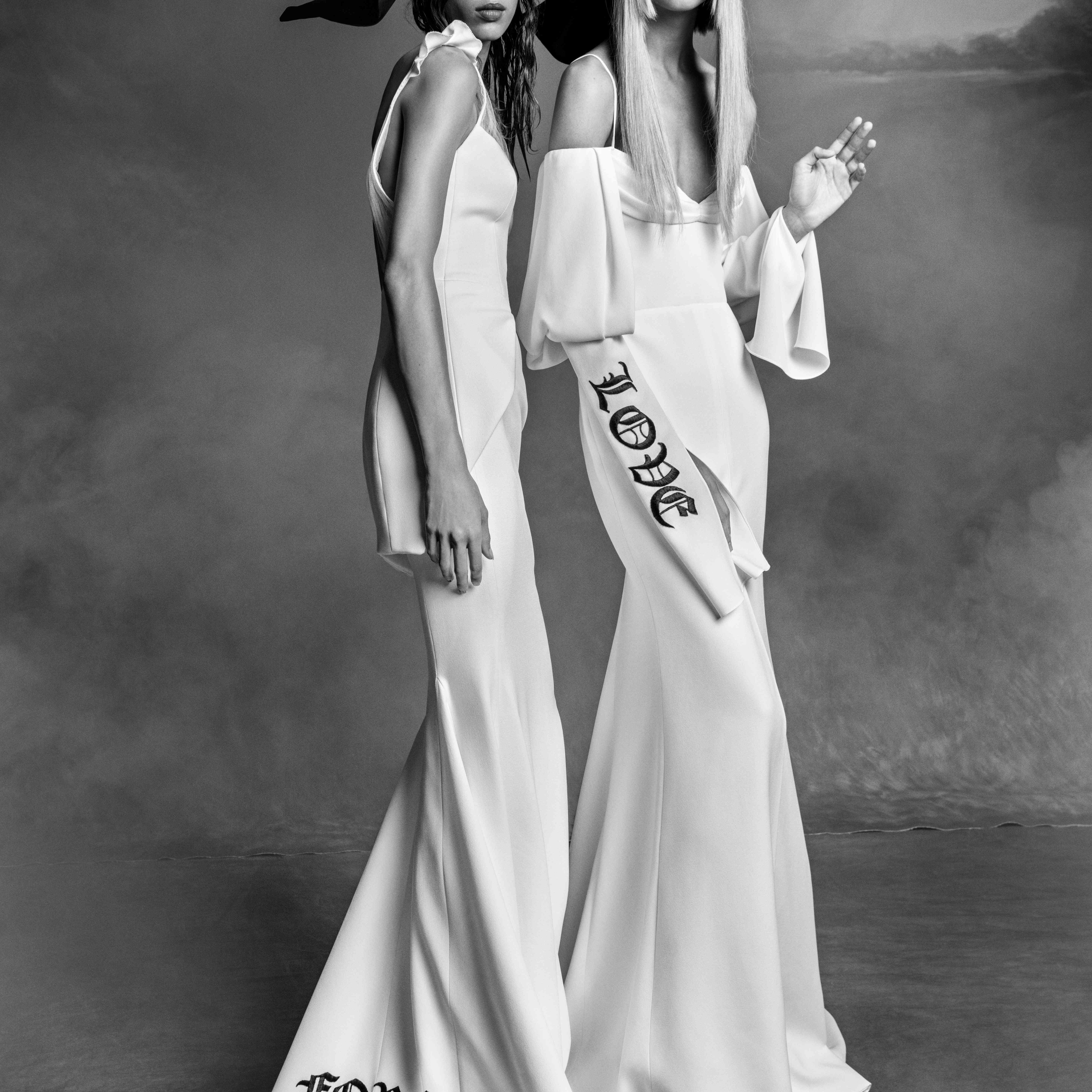 Two models in white bridal gowns, the one on left with the word