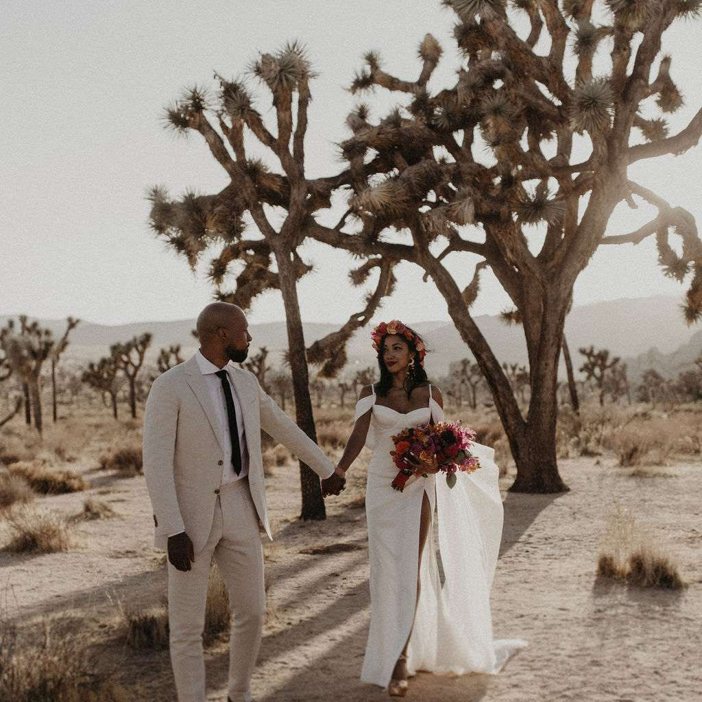 Bride and groom holding hands in Joshua Tree National Park