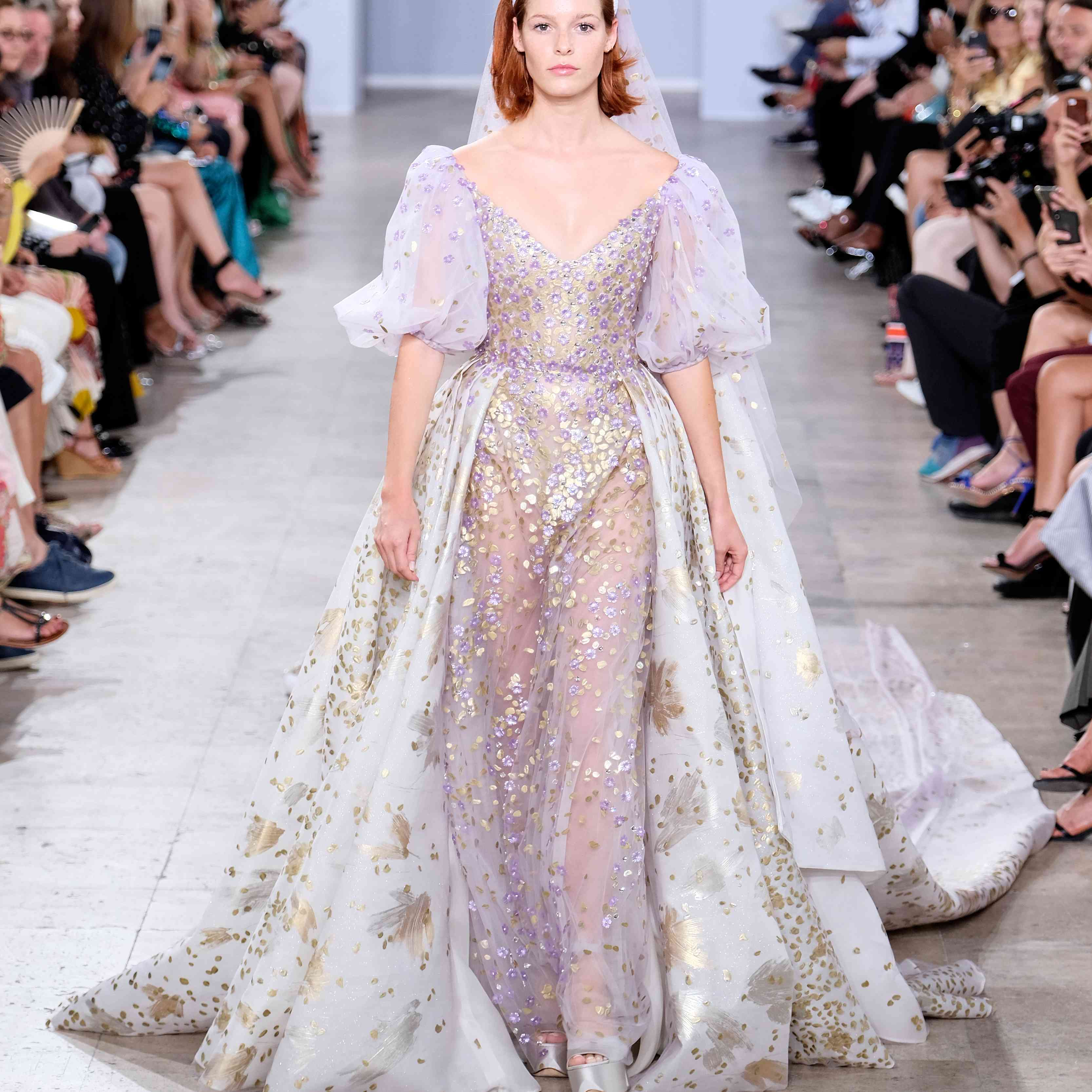 Model in gold-accented lilac and white gown with puffy sleeves