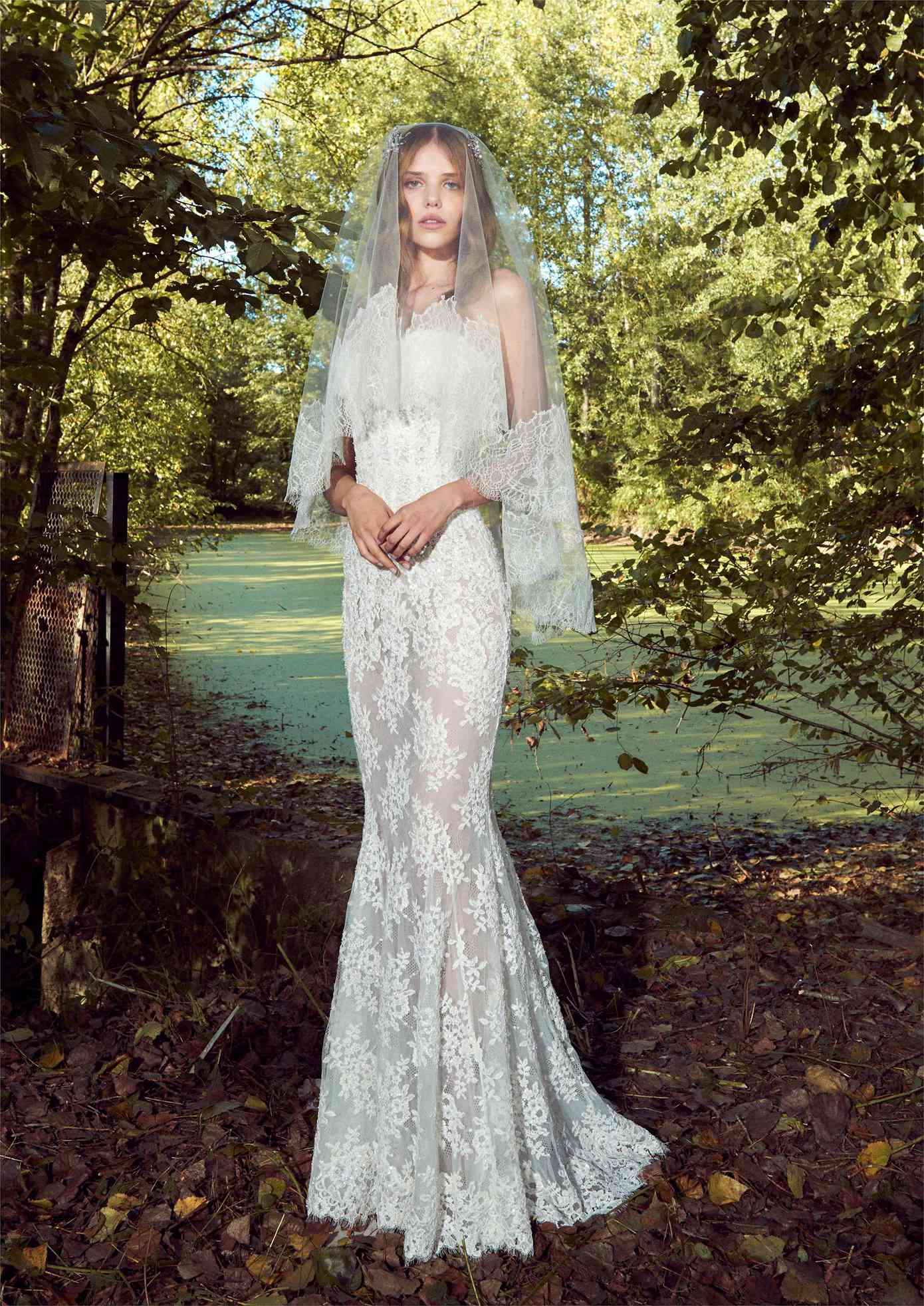 Model in a strapless tulle mermaid gown with lace embroidery and eyelash lace trim with a matching veil