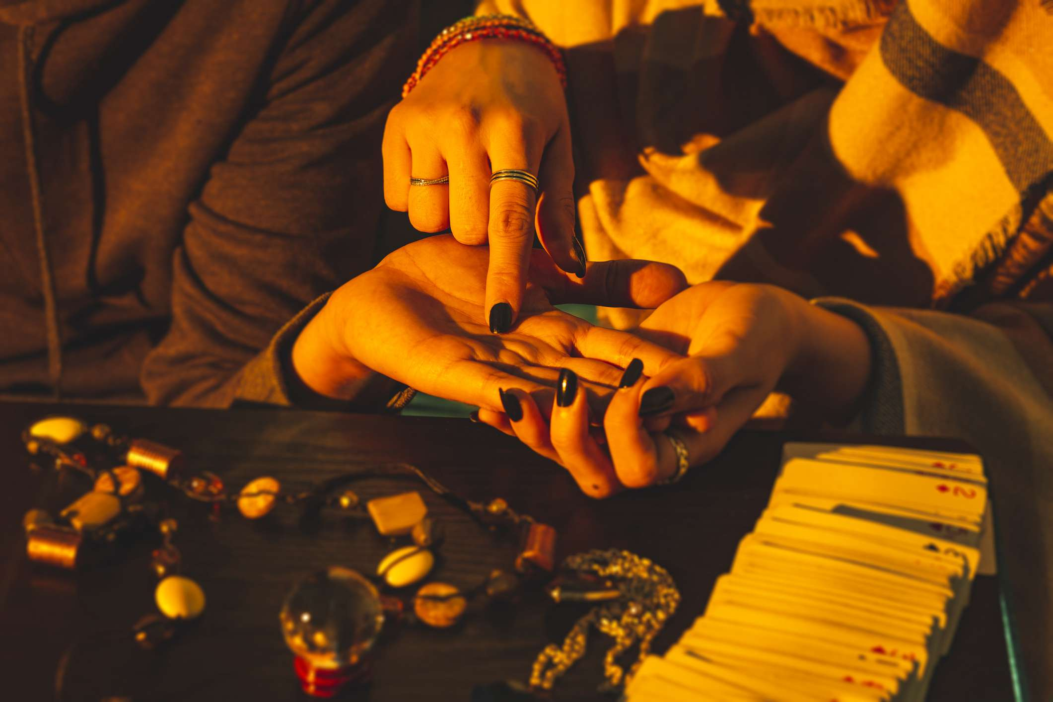 Palm reader holding a person's hand, pointing out palm lines