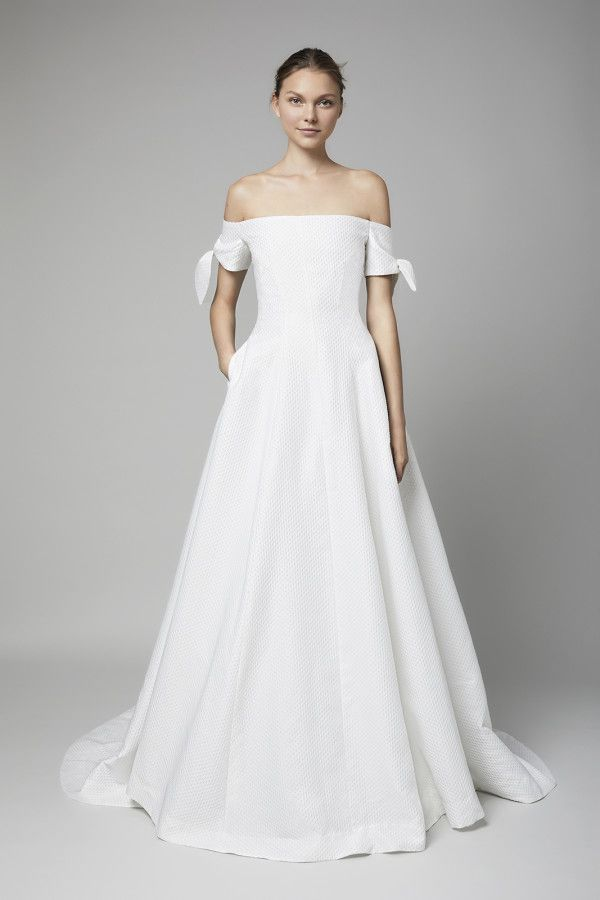 Model in off-the-shoulder white wedding gown with pockets