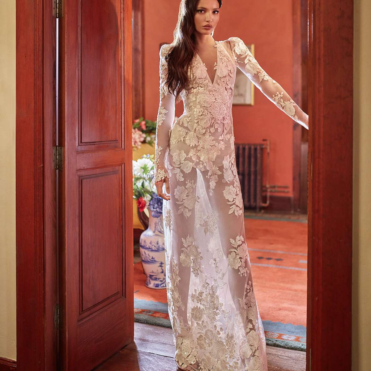 Model in allover lace sheet wedding gown with long sleeves