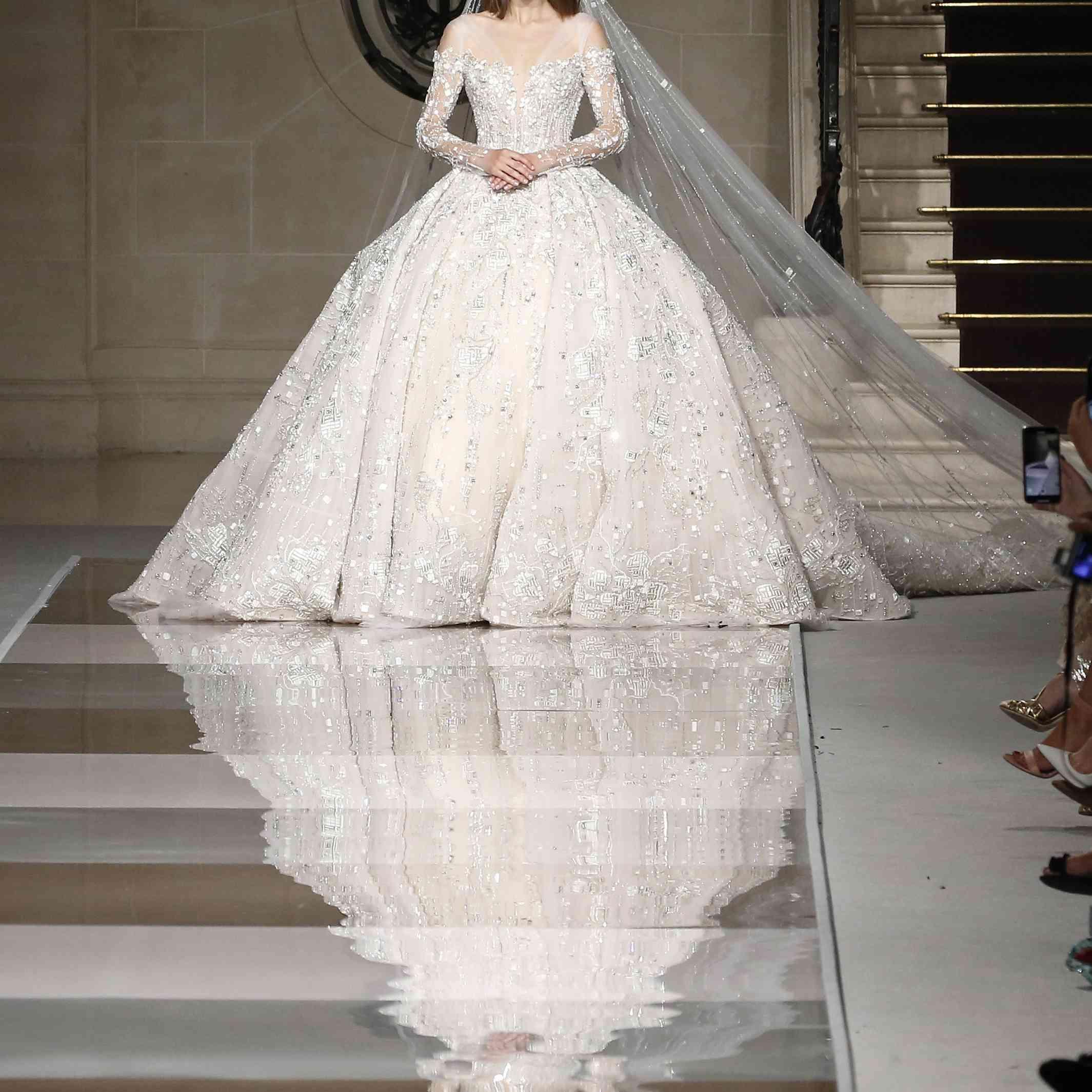 Model in off-the-shoulder, long-sleeved, embellished princess gown