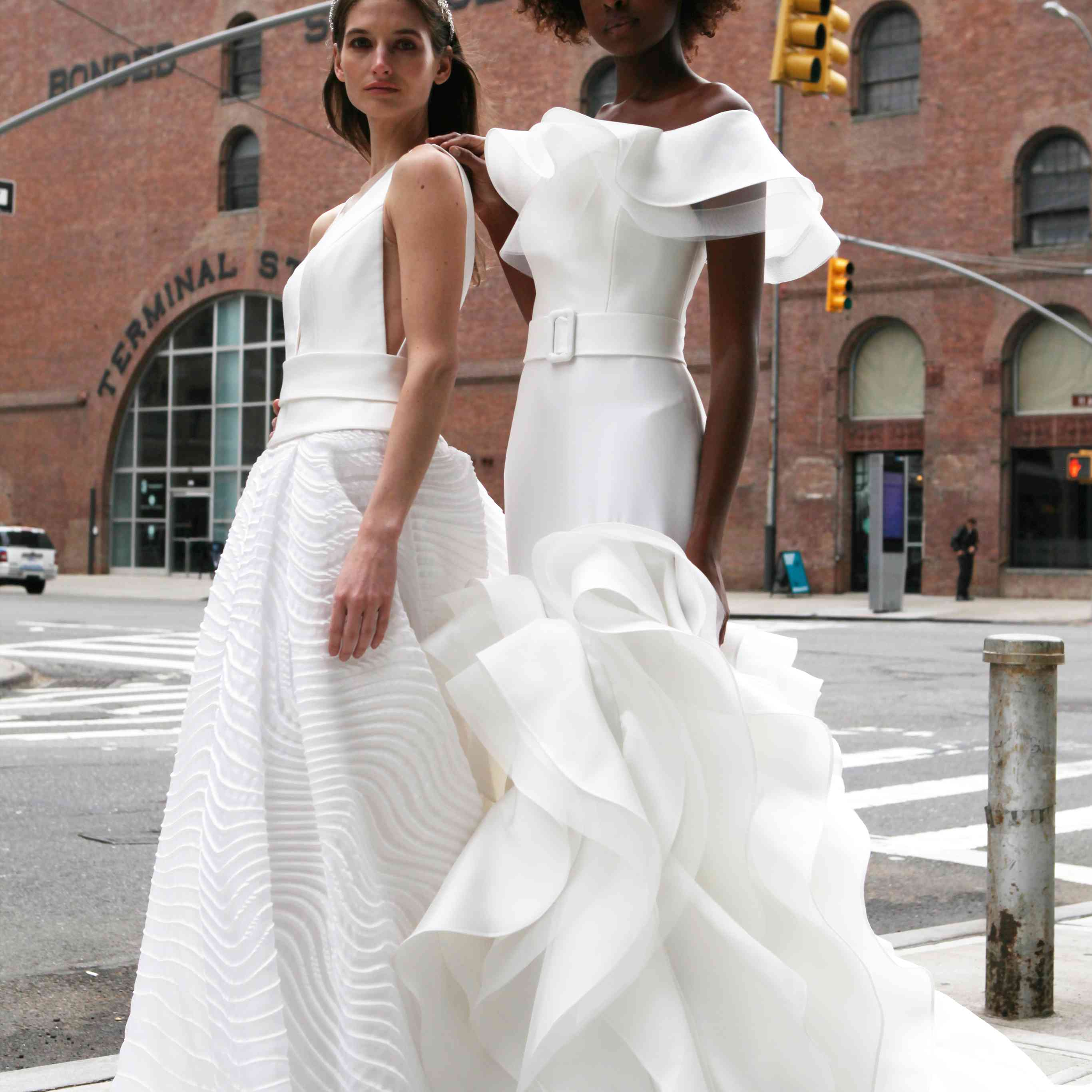 Two models standing on a sidewalk, one in a crepe ballgown (left) and the other in a ruffled fit-and-flare crepe gown