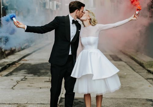 Bride and groom with blue and red smoke bombs.