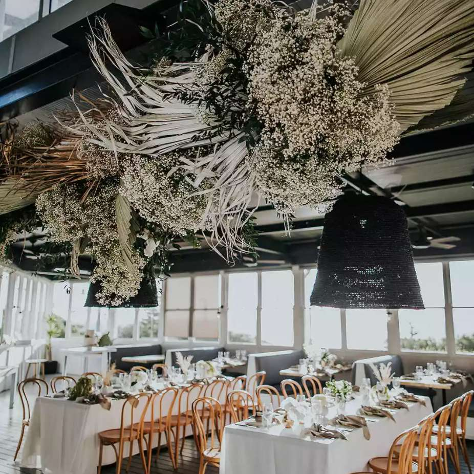 a dramatic overhead arrangement of baby's breath and dried palm leaves