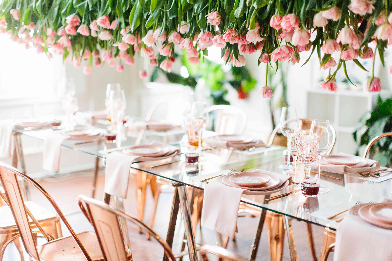 Pink tulip floral chandelier above a set table