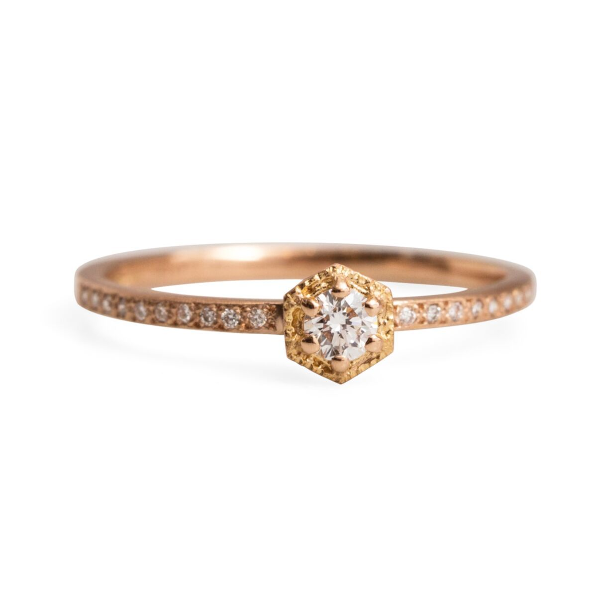 Brilliant-cut diamond in a gold hexagonal setting with a diamond pave band