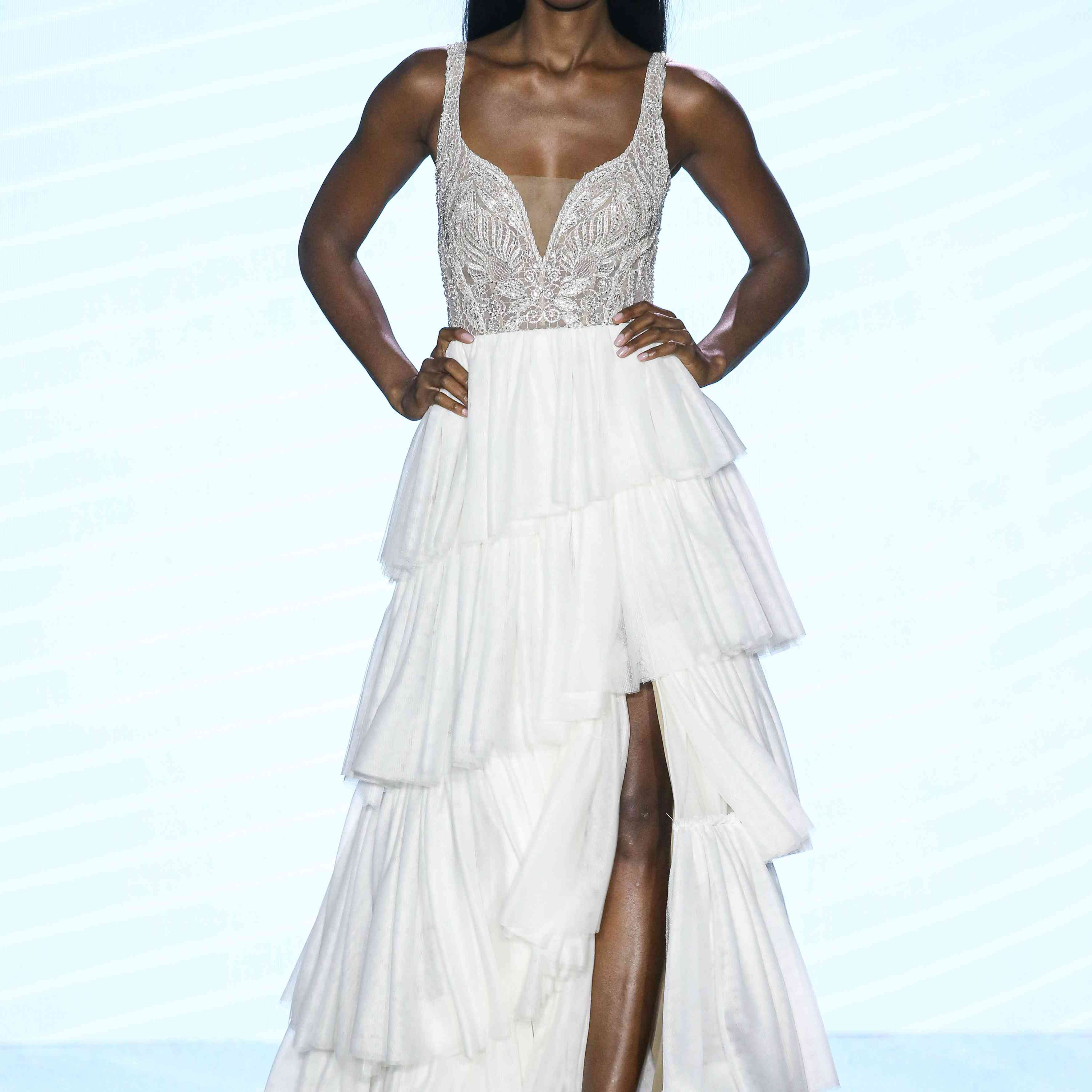 Model in A-line wedding dress with a V-neck jeweled bodice and a tiered tulle skirt with front slit