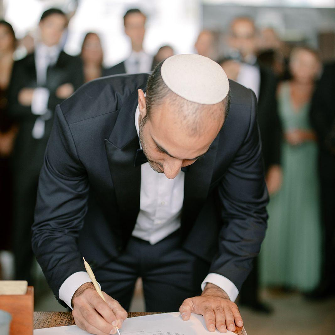 groom signing ketubah