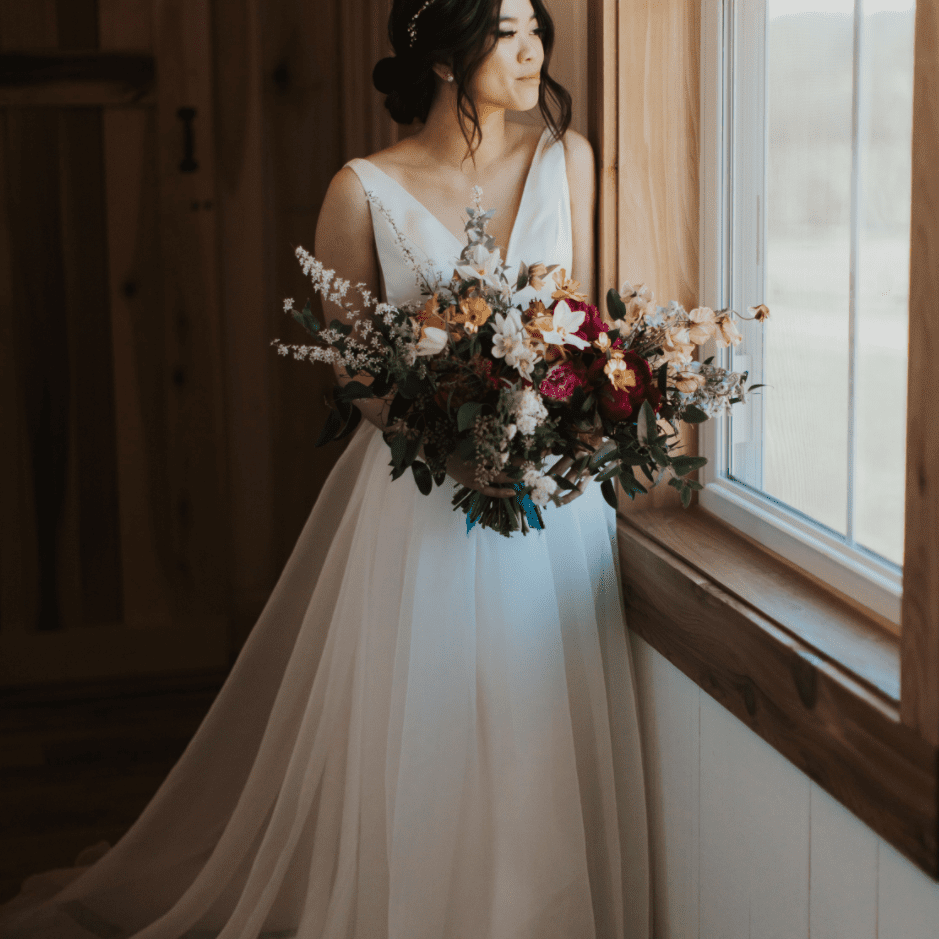 Bride holding bouquet by a window