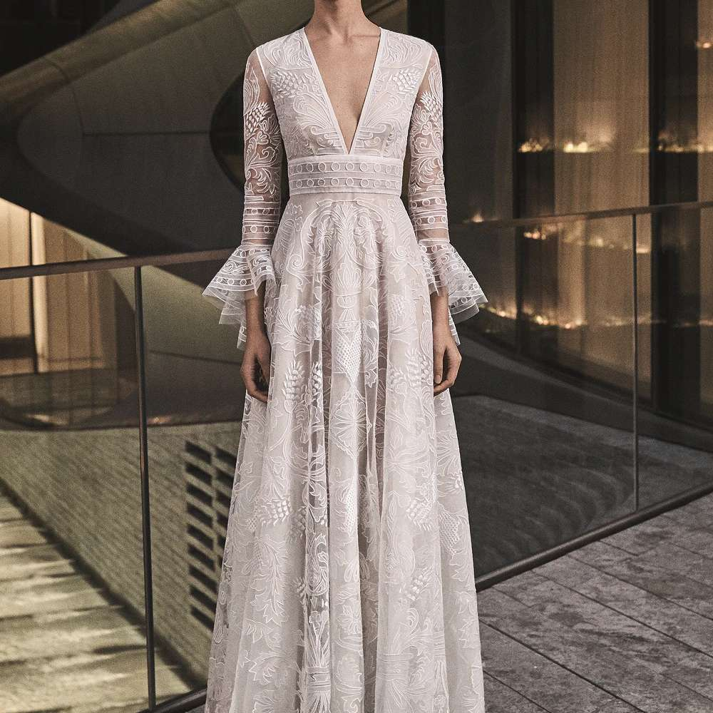 Model in long-sleeve embroidered V-neck gown with ruffle cuffs