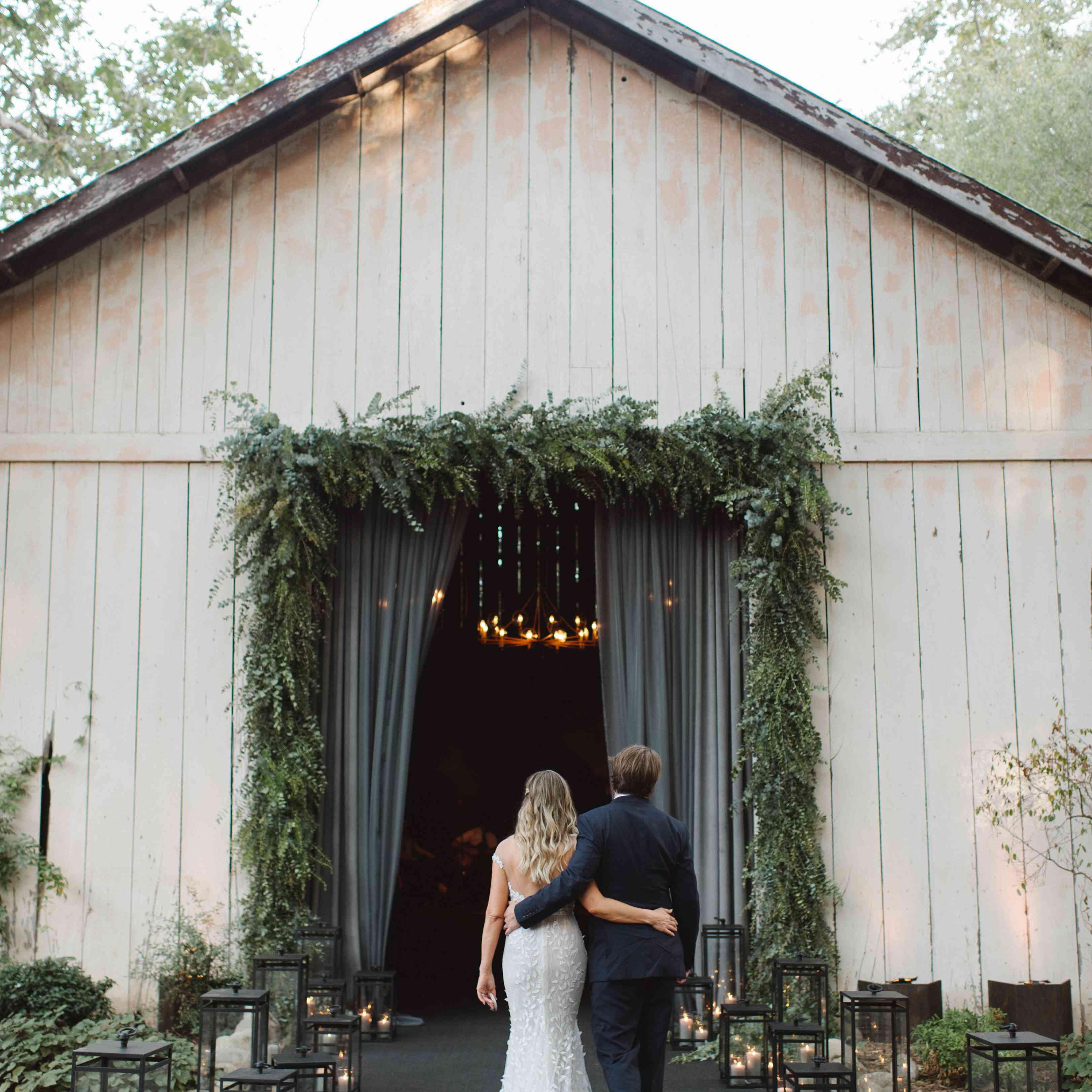 bride and groom walking into barn venue