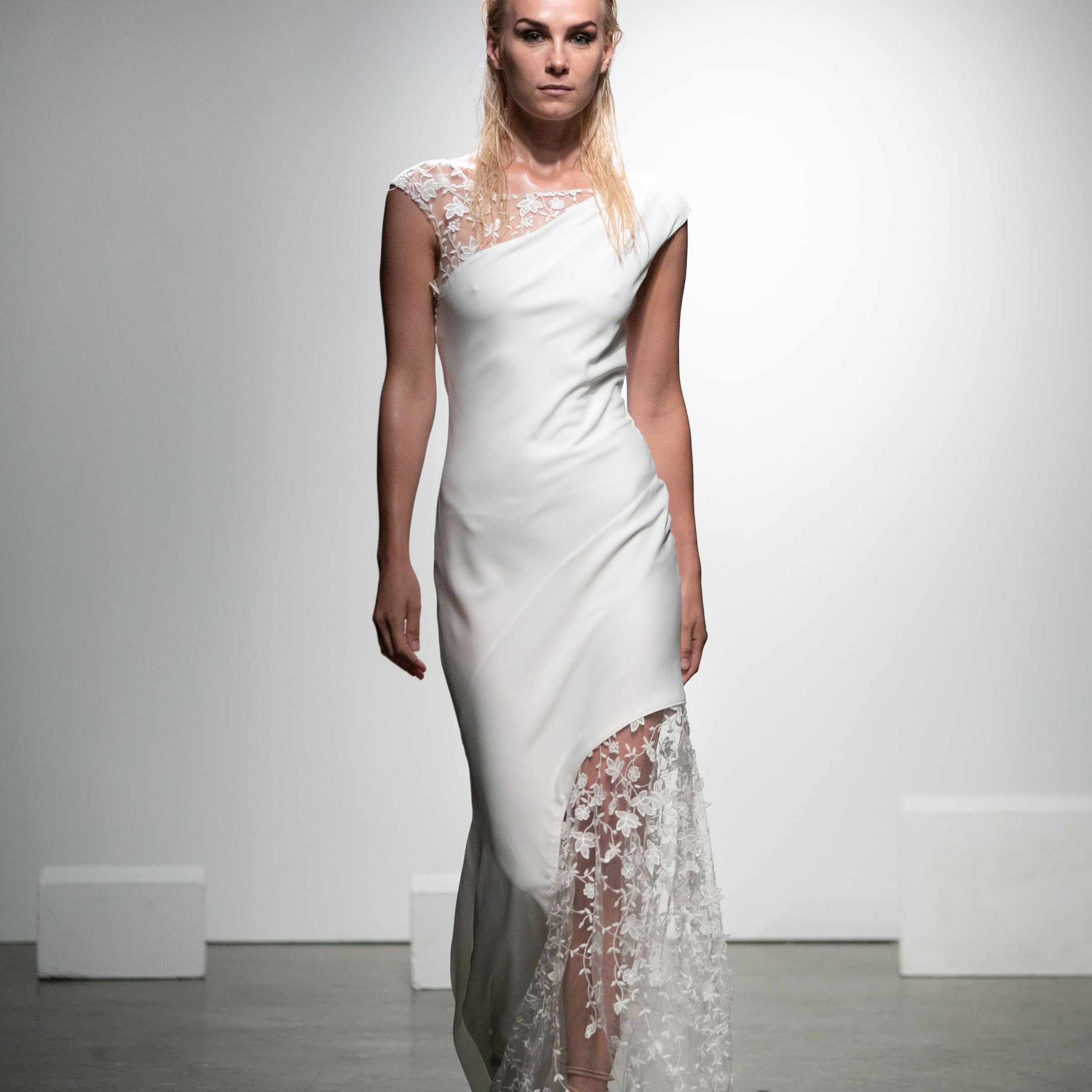 Model in asymmetrical crepe dress with floral-embroidered tulle and cap sleeves