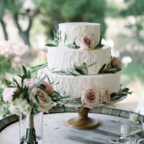 A classic floral wedding cake made rustic with decorative eucalyptus leaves by Edelweiss Bakery