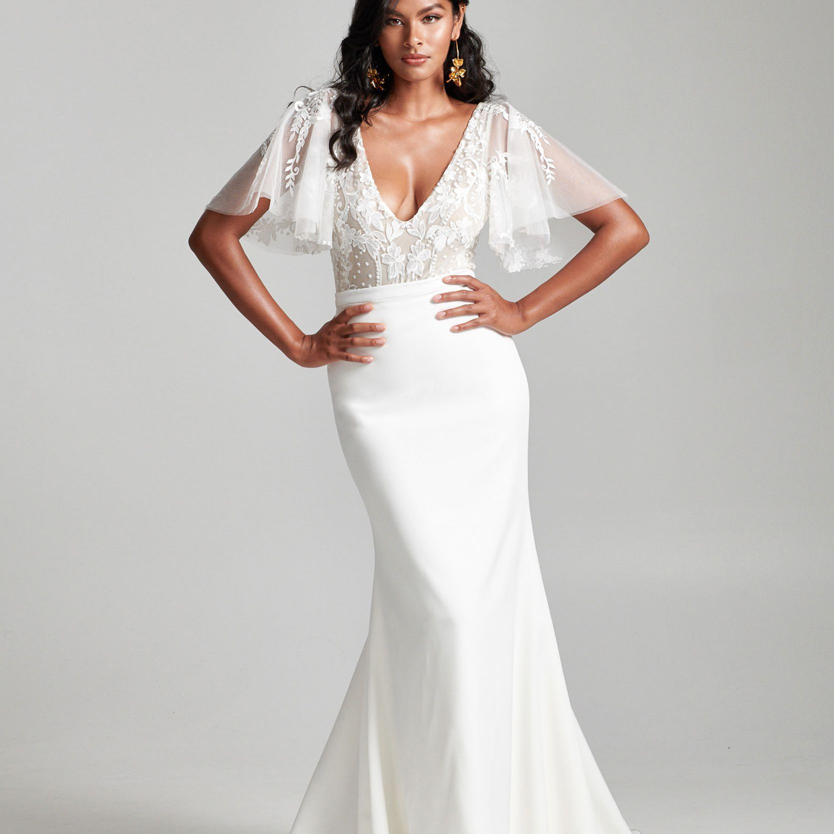 Model in lace top with flutter sleeves and long skirt