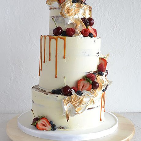 A three-tiered white wedding cake dripping with caramel, rustic fall fruits, and torched marshmallow fluff by Miss Ladybird Cakes