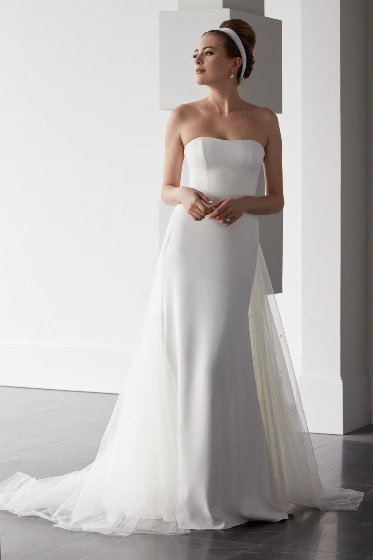Model in strapless crepe column gown with a tulle train