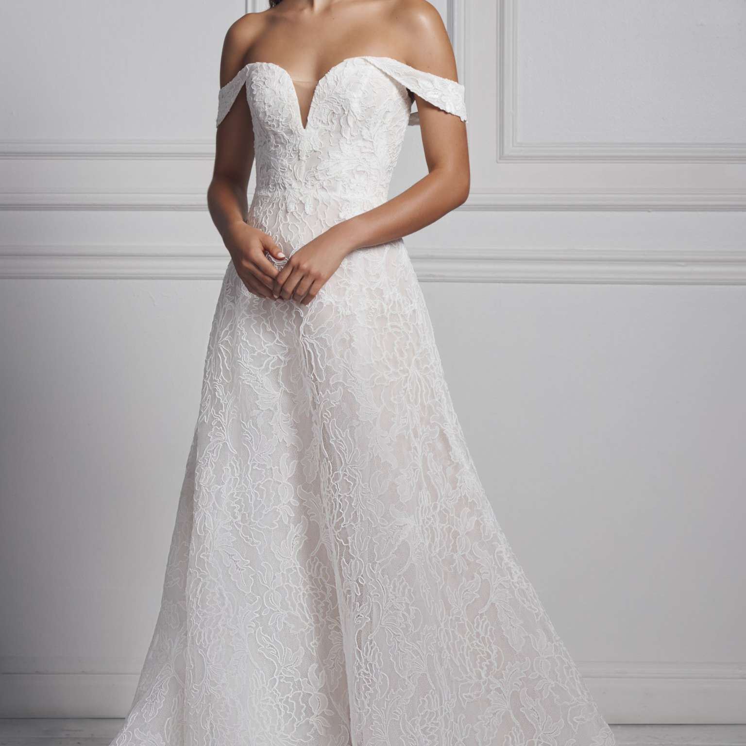 Model in off-the-shoulder lace ballgown with illusion neckline