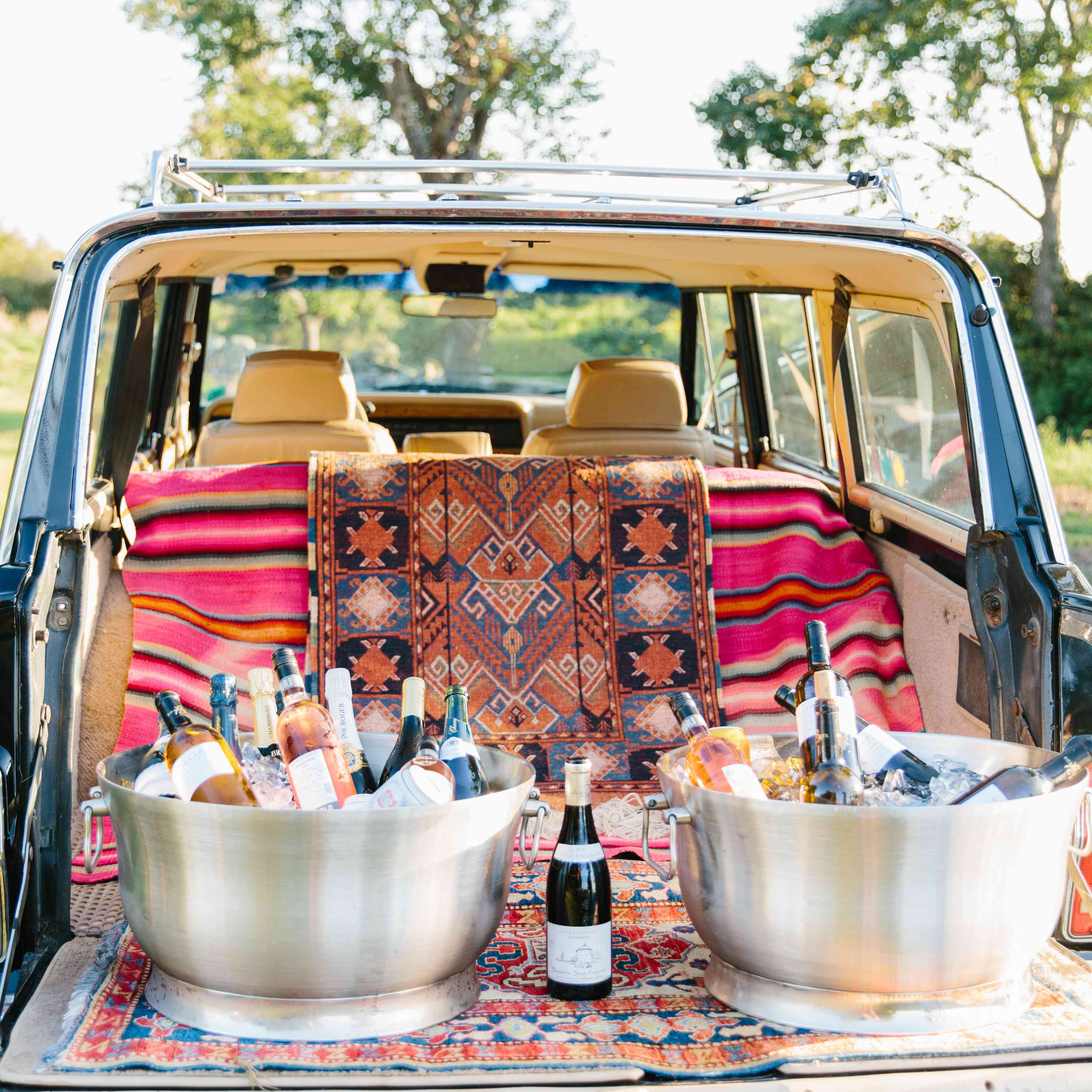Trunk of car with rugs and champagne/wine on ice