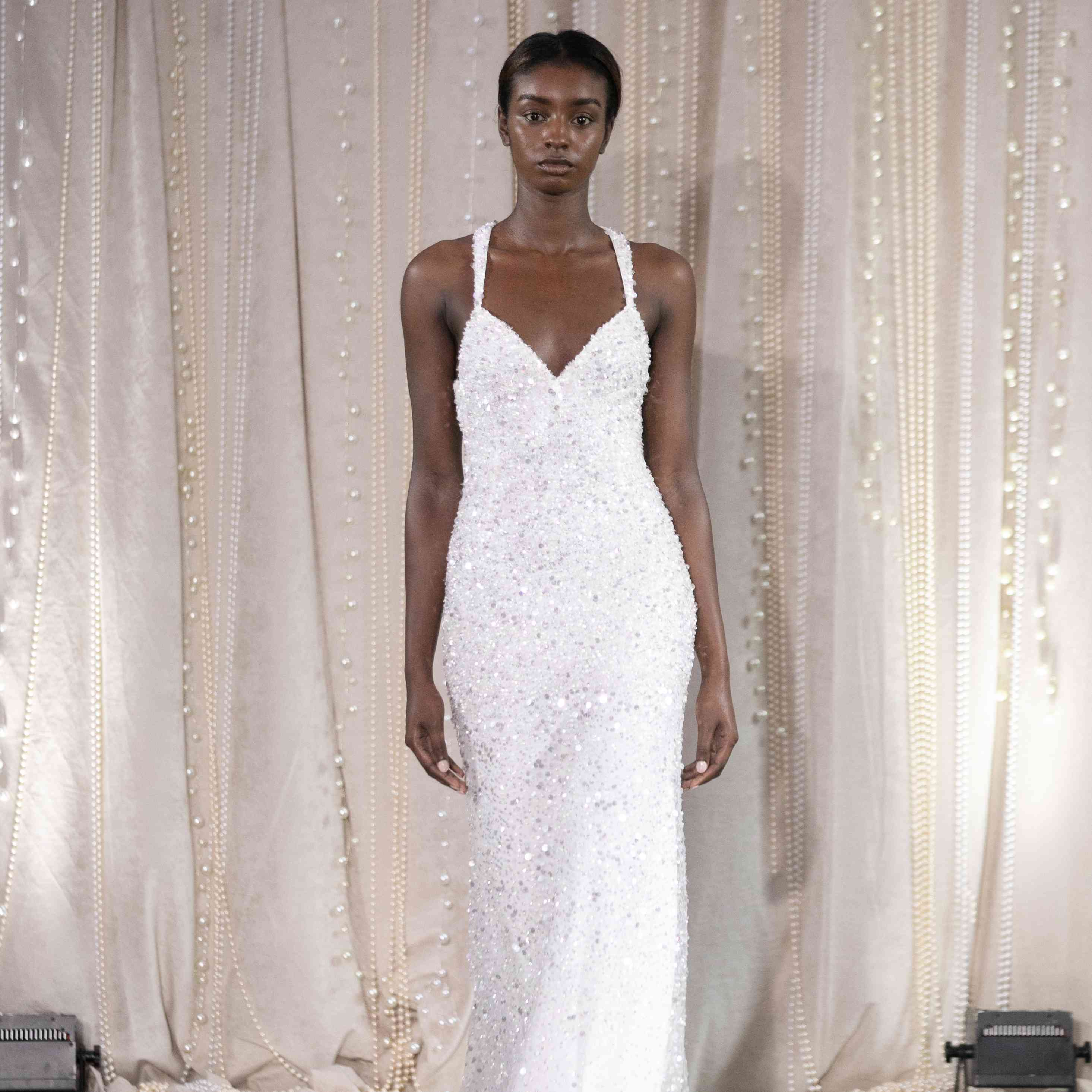 Model in sleeveless beaded fitted wedding dress