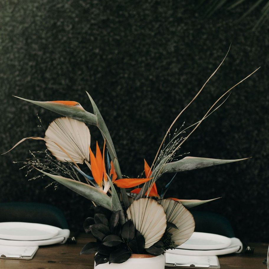 Centerpiece arrangements of dried palm leaves and birds of paradise