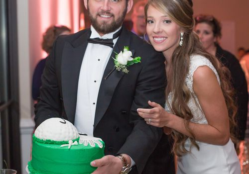 Couple holding a golf-themed groom's cake at their wedding