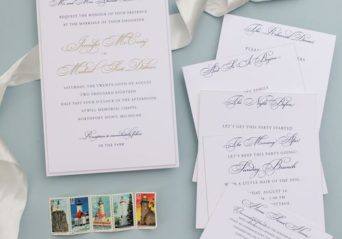 invitation suite on blue background with lighthouse stamps