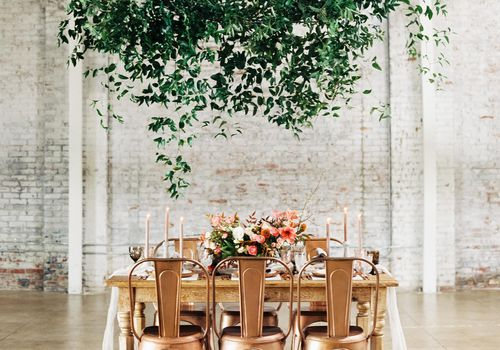 Loose hanging greenery garland over intimate wedding reception table