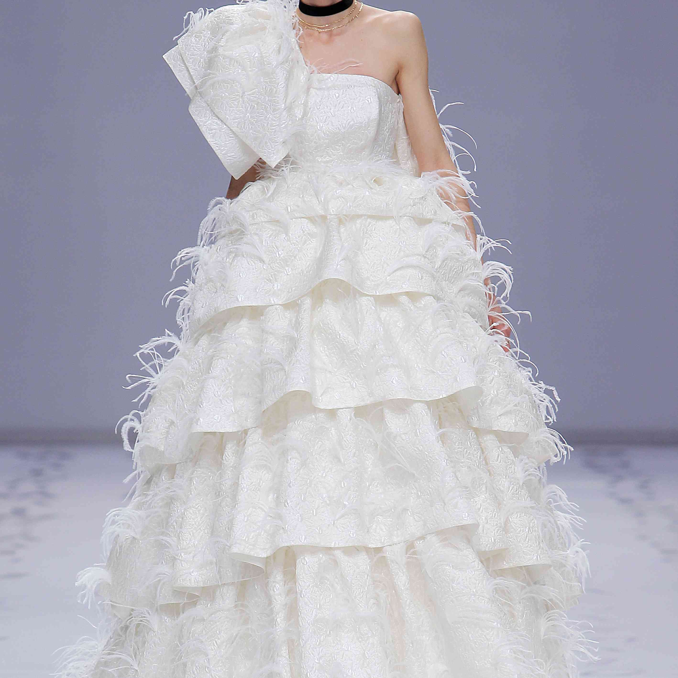 Model in a one-shoulder silk princess gown with floral imprints and ostrich feathers featuring a pleated asymmetrically tiered skirt