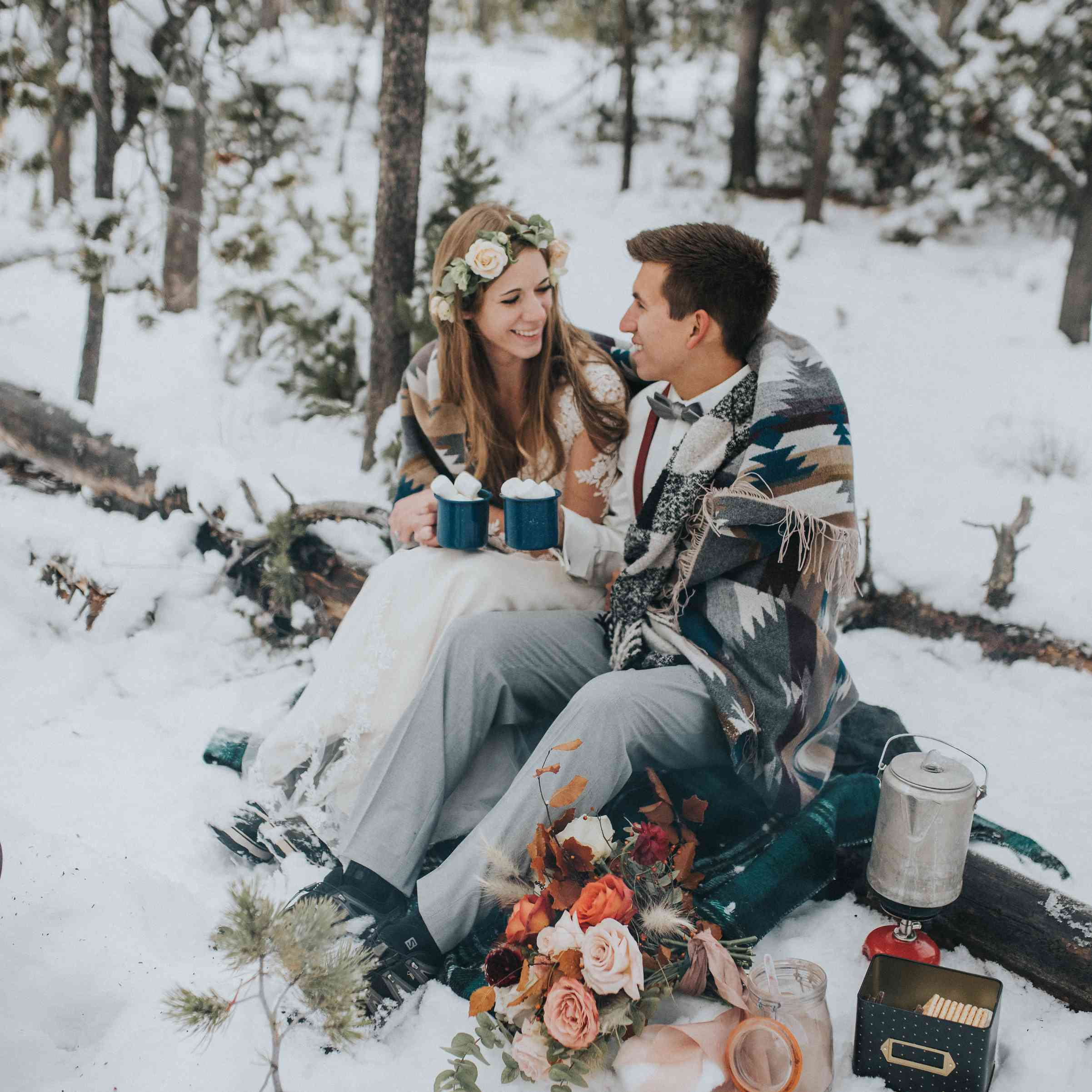 Bride and groom sitting on a log with a blanket and mugs of cocoa