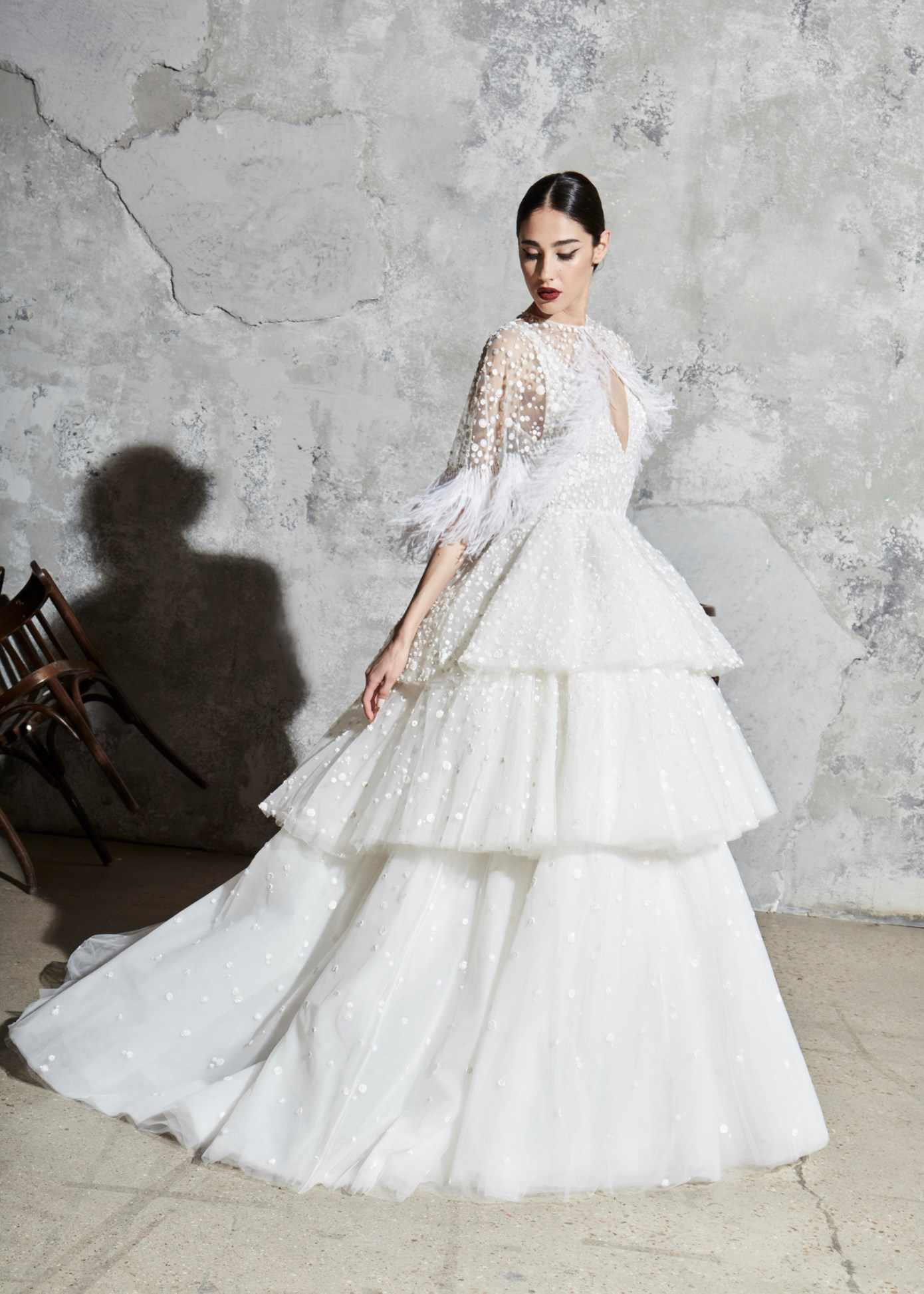 Model in V-neck ballgown with sequins and a three-tiered skirt with a matching sheer tulle shrug with feather detail