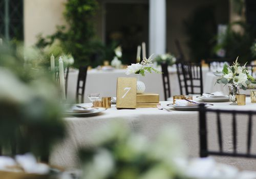 Dining table at an outdoor wedding reception/dinner party. Table is complete with place settings, flower arrangements and gold decor with number seven.