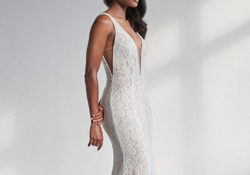 Model in allover lace mermaid gown with plunging illusion V neckline and illusion cutout sides