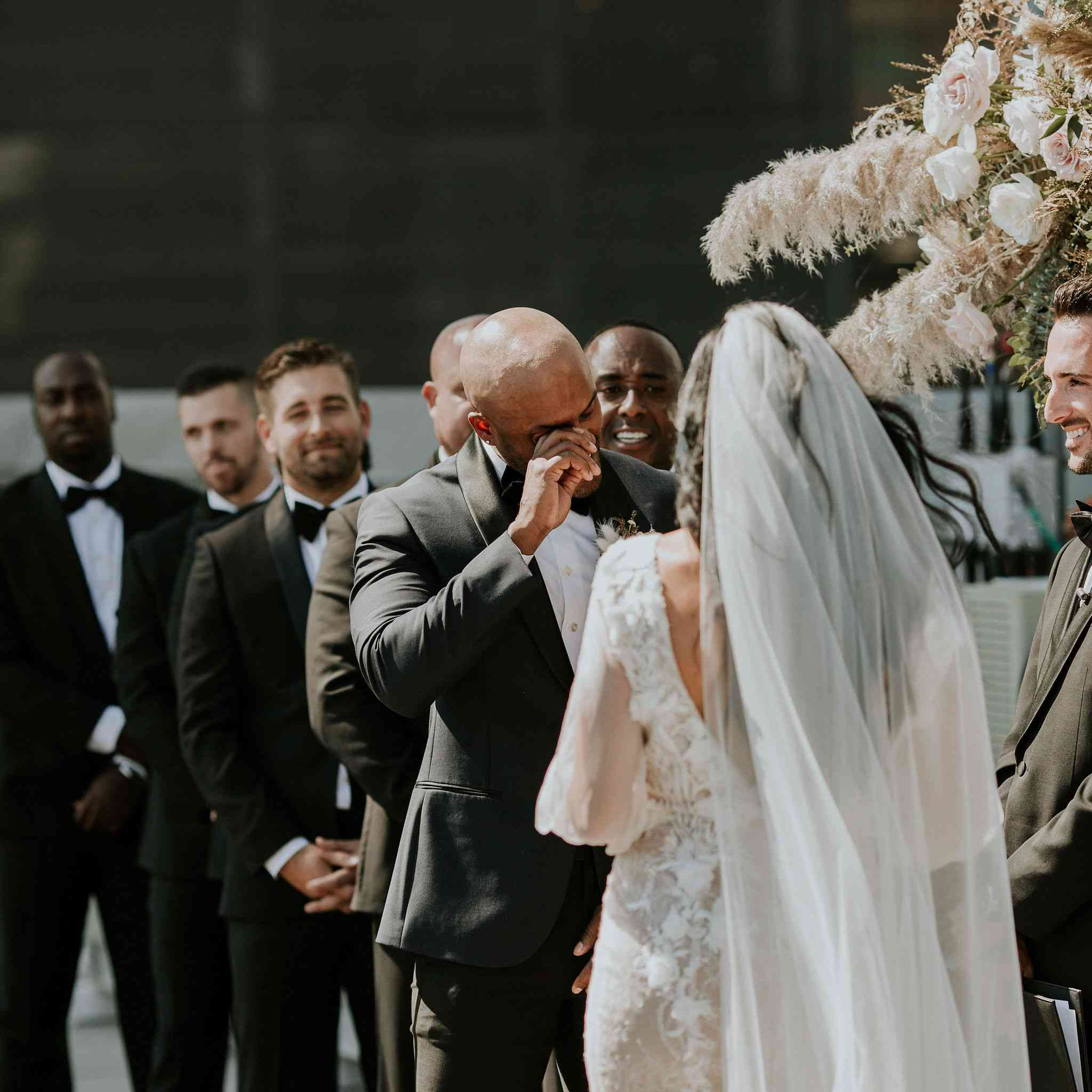 Groom wiping tears at wedding ceremony altar