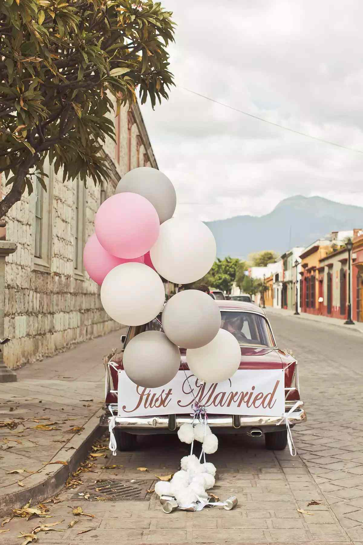 Pink, white and gray balloons attached to a getaway car