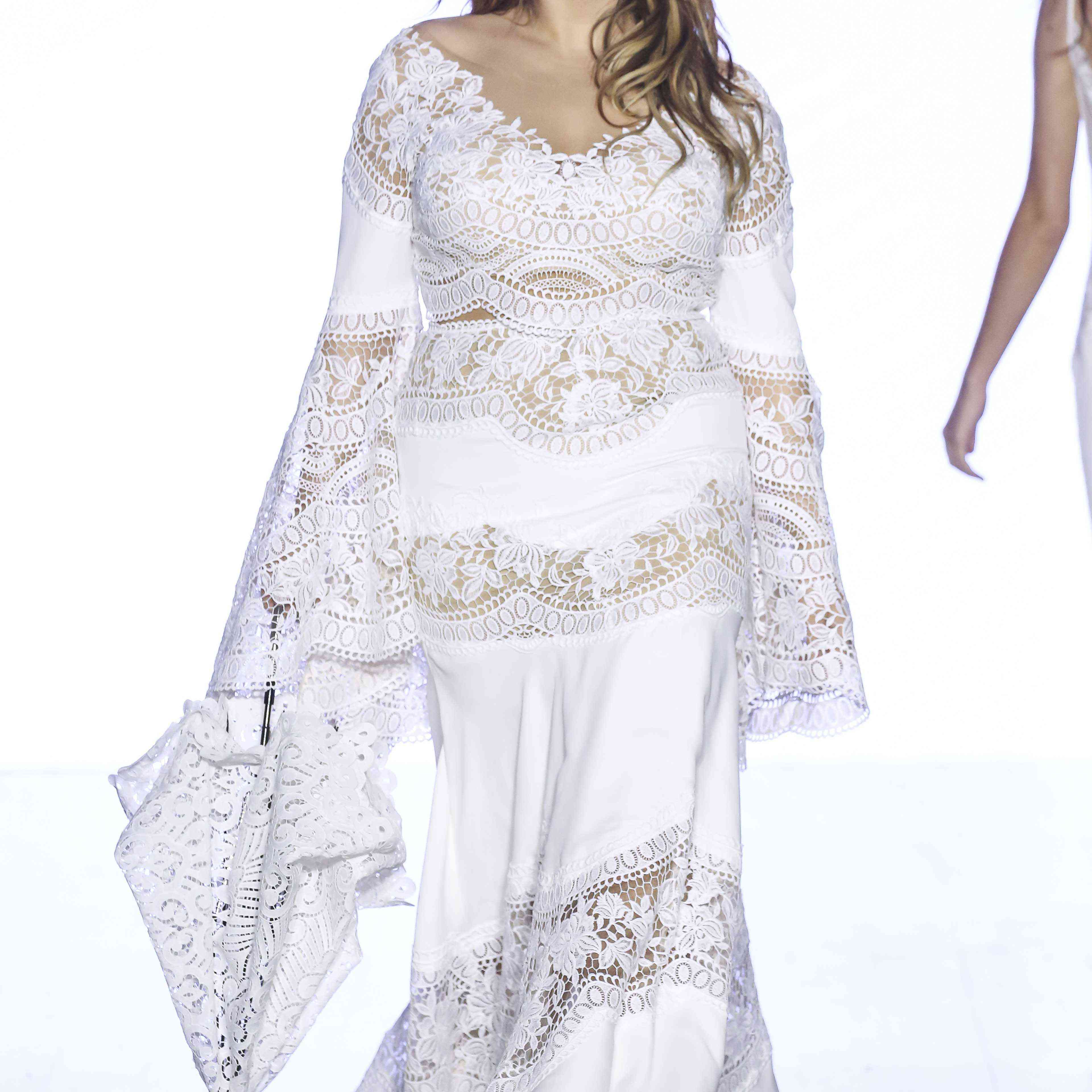 Model in flared-sleeve lace crop top with matching full-length skirt