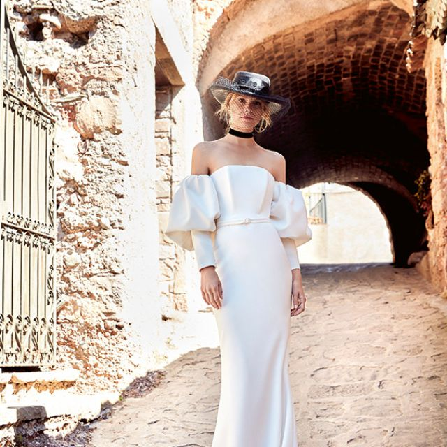 Model in off-the-shoulder crepe gown with puff sleeves and long cuffs