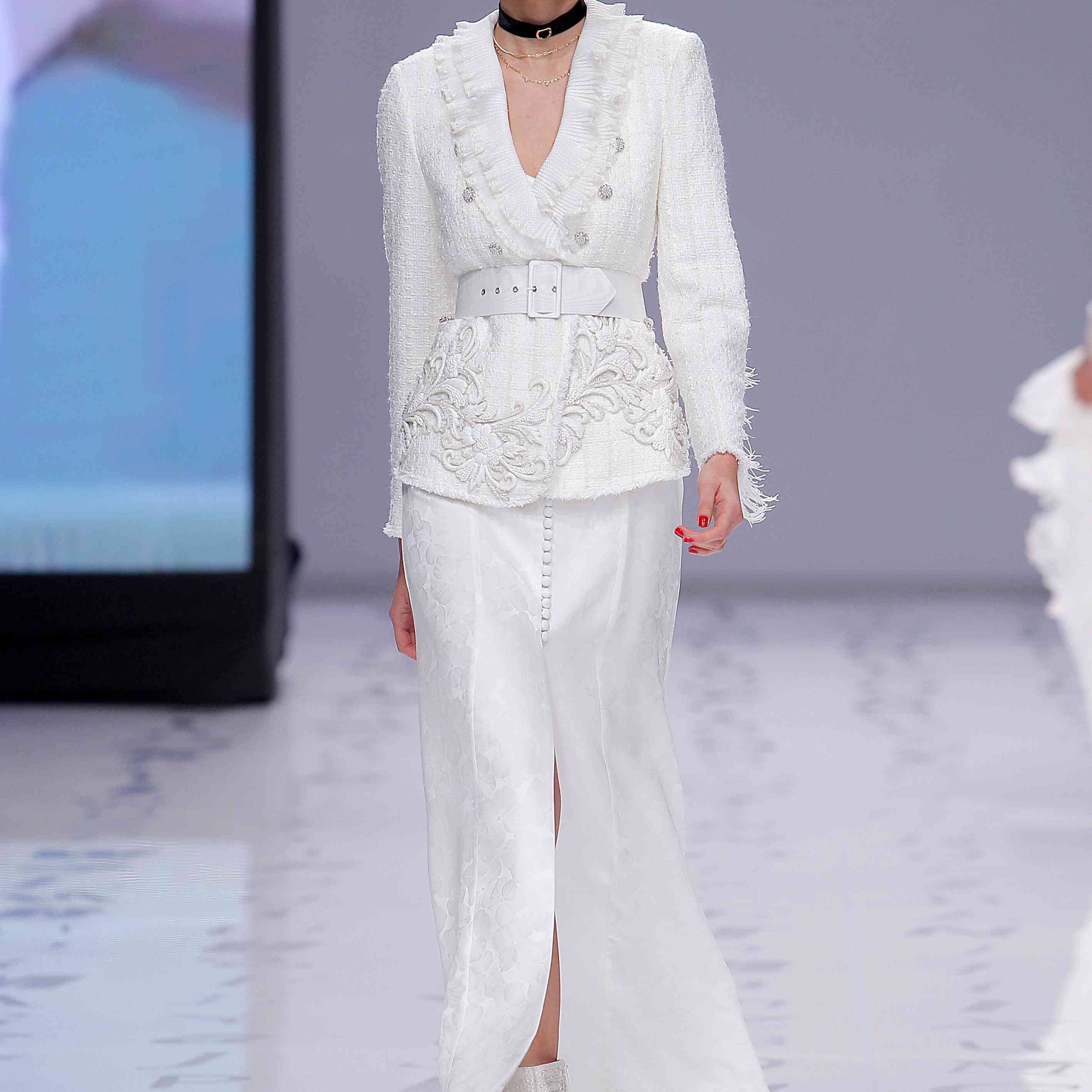 Model in a ruffled and embroidered bridal blazer with an open-front floral silk skirt and a matching cap