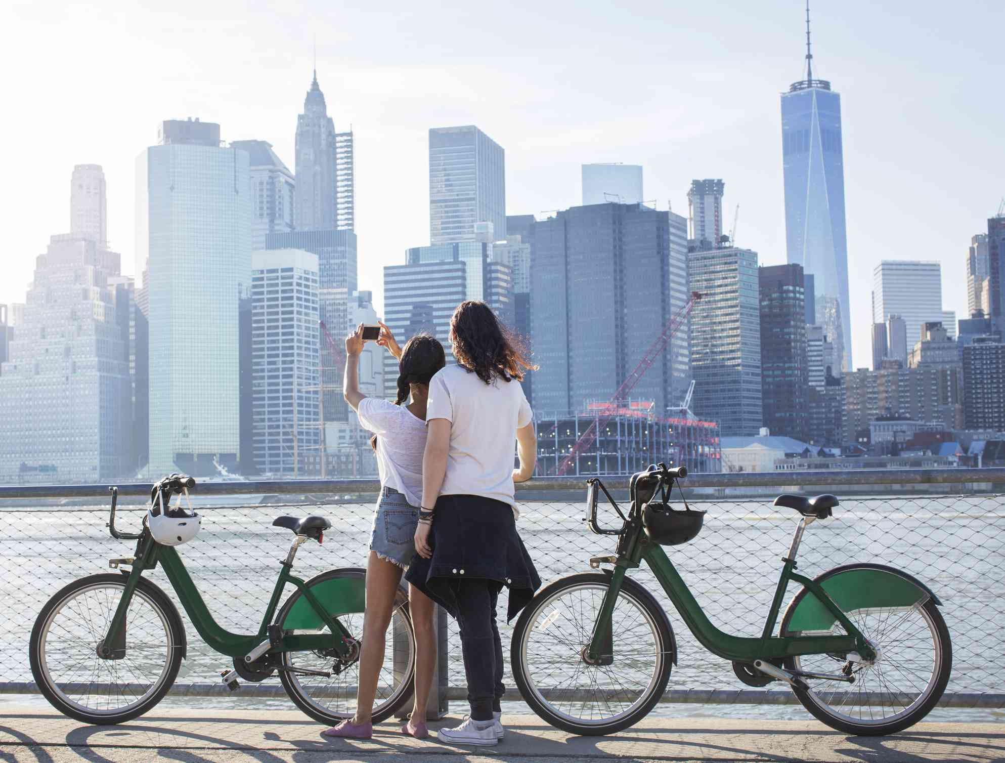 Couple with rental bikes and skyline in background