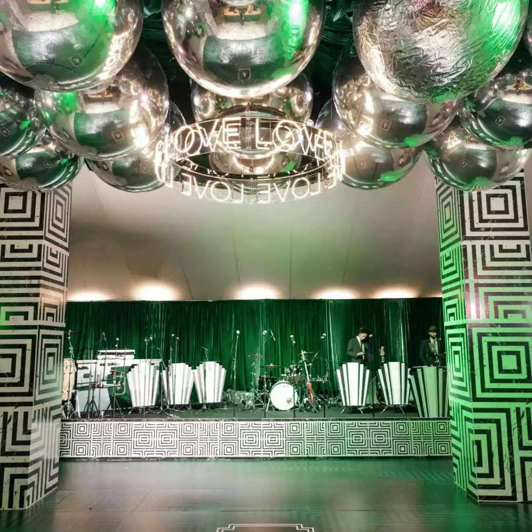 Neon sign and disco balls over dance floor