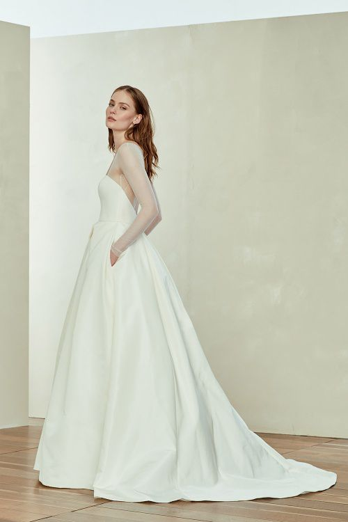 Model in long white wedding ball gown with skirt pockets