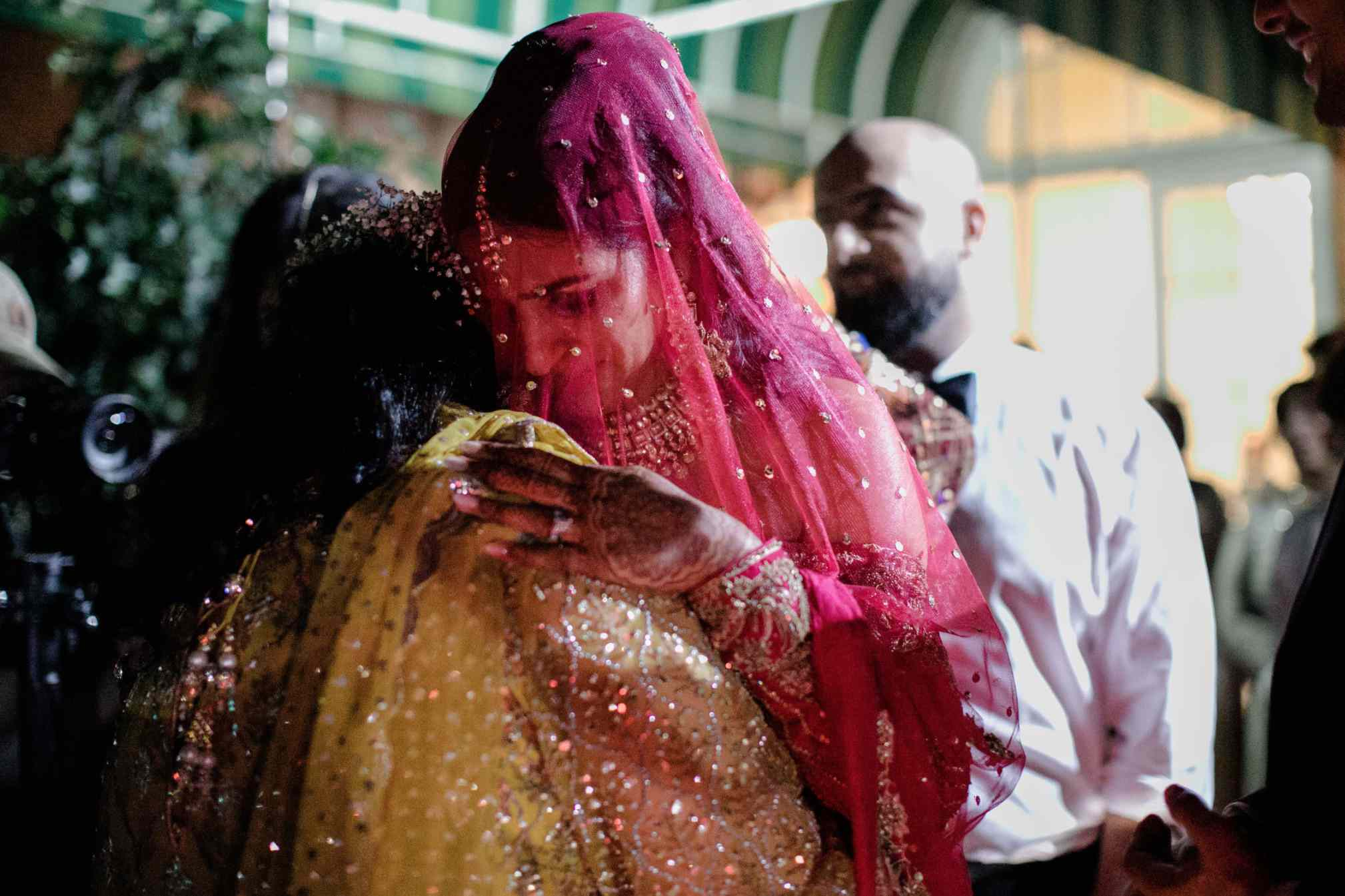 South Asian bride hugging mother in emotional farewell