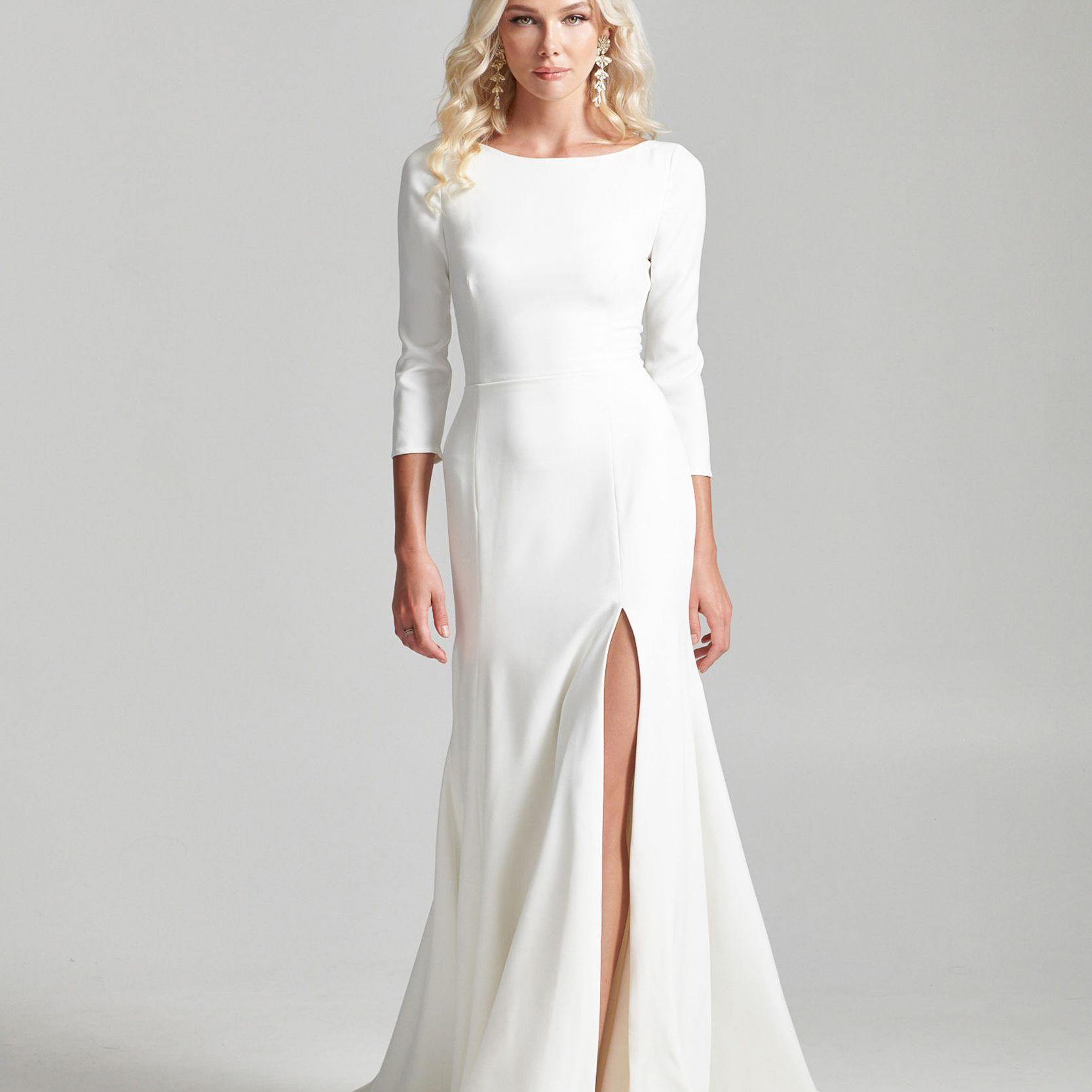 Model in three-quarter sleeve white wedding dress with skirt slit