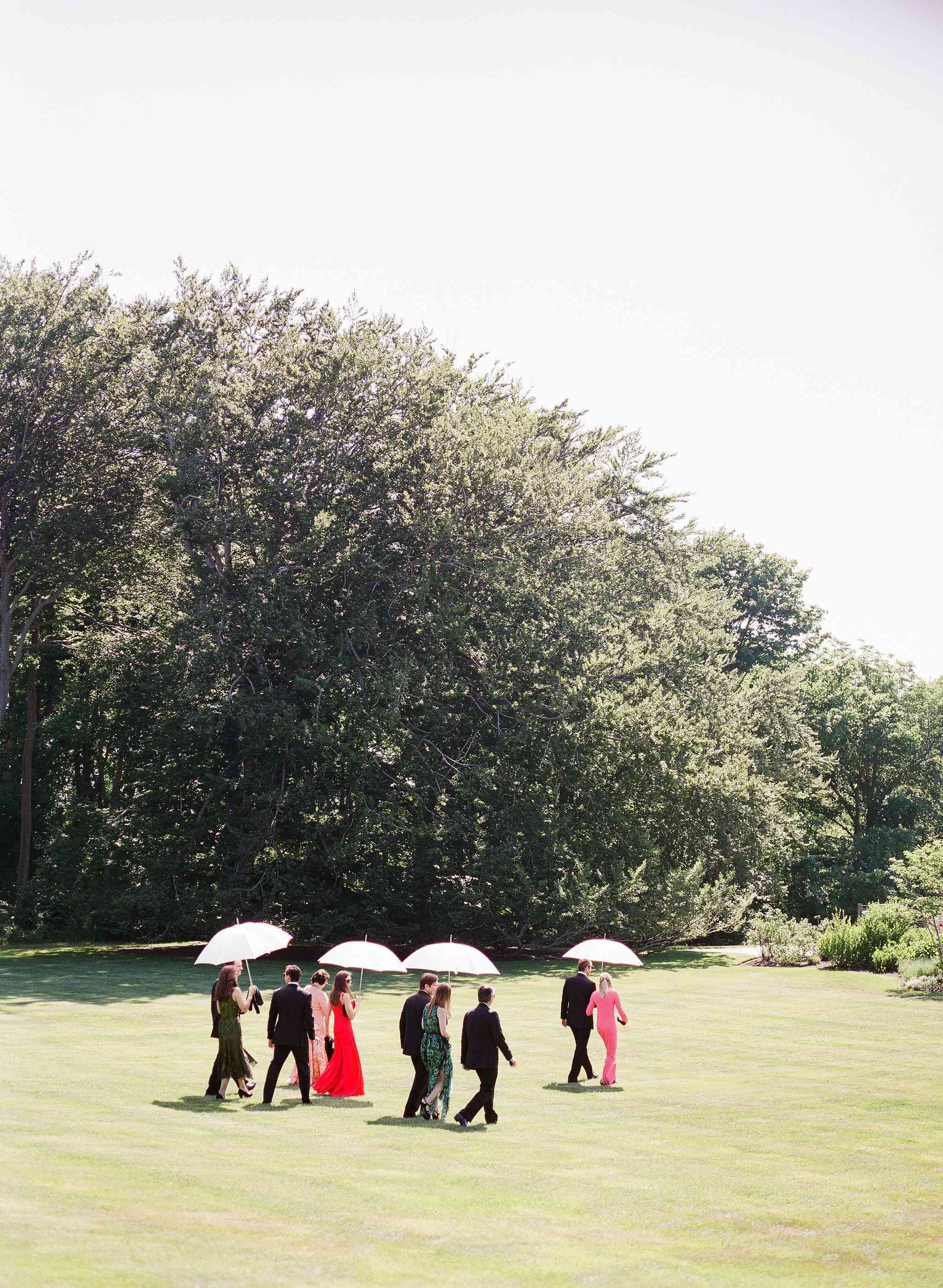 Guests walking to a wedding holding umbrellas